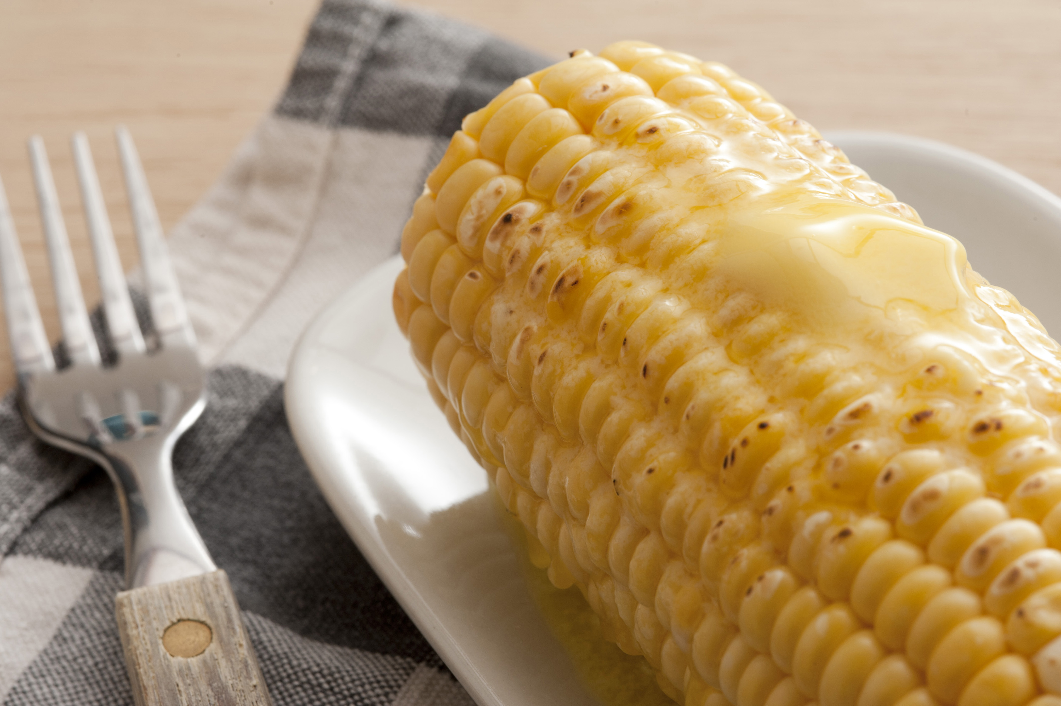 Close-up of cooked corn-cob with butter on top lying on plate with fork
