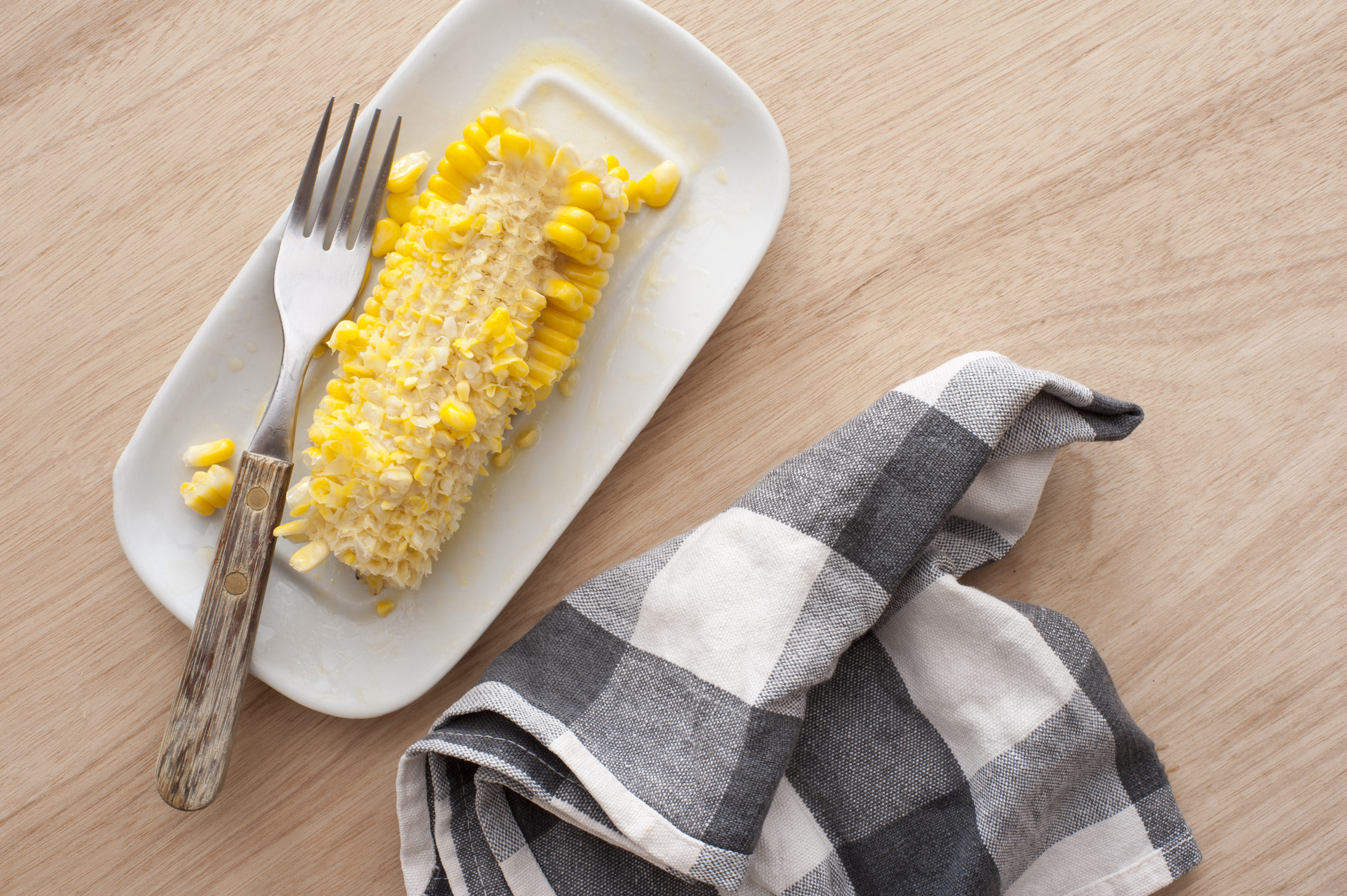 Eaten corn cob on white plate with fork and checked napkin. From above