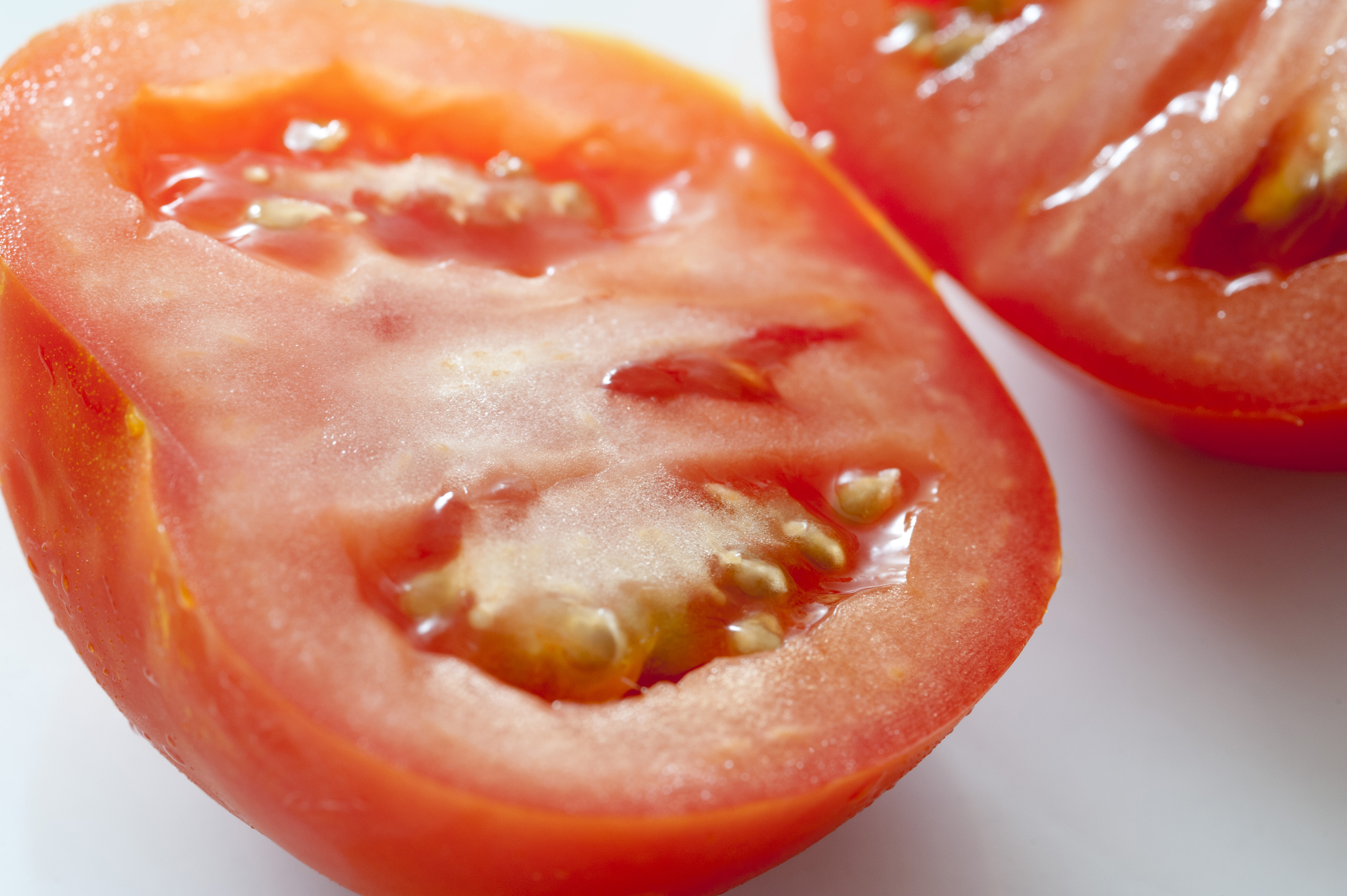 Fresh halved ripe tomato viewed close up at an oblique angle to show the juicy texture of the pulp