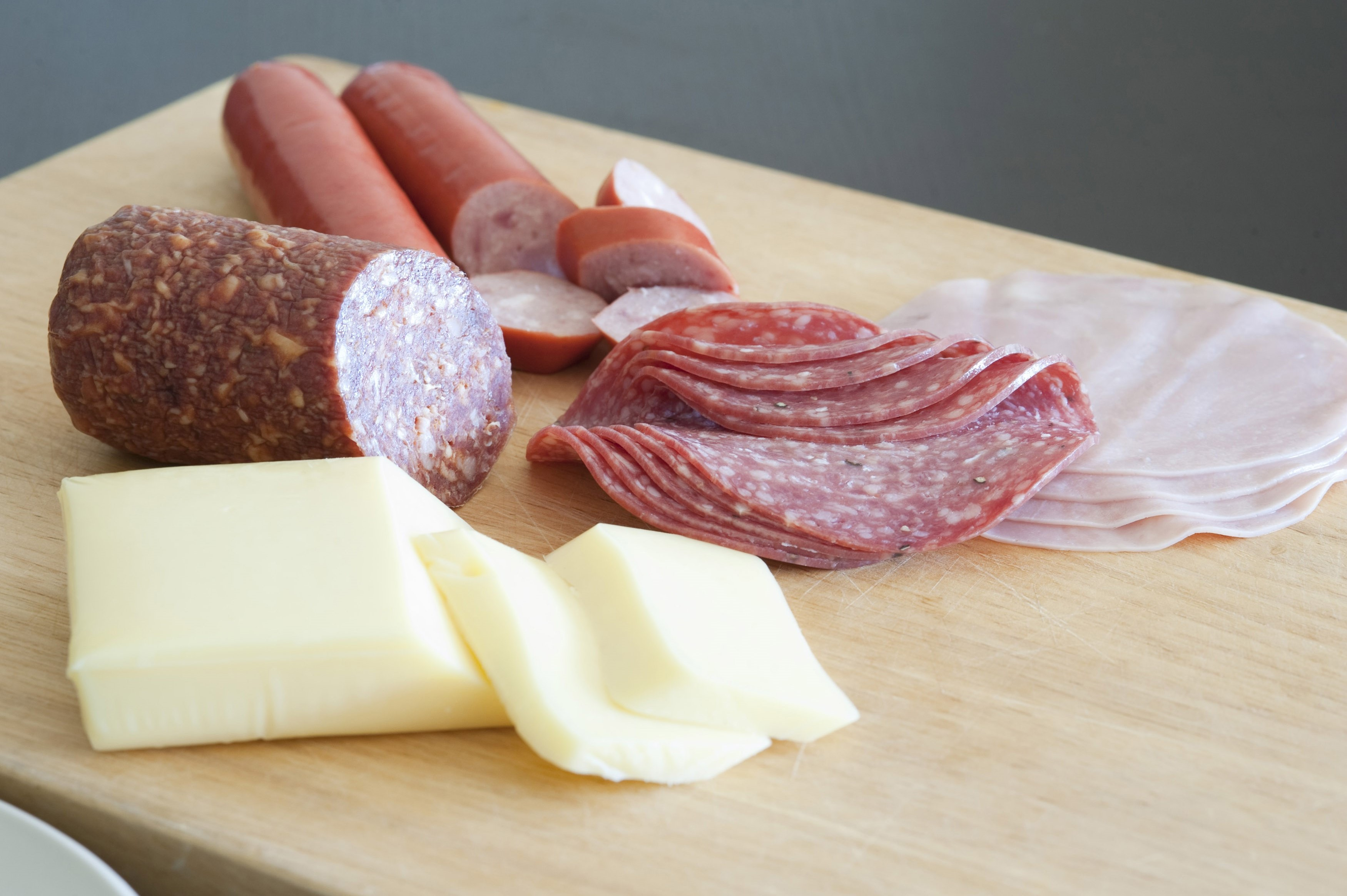 German breakfast laid out on a wooden chopping board with thinly sliced salami and cold meats and portions of fresh cheese