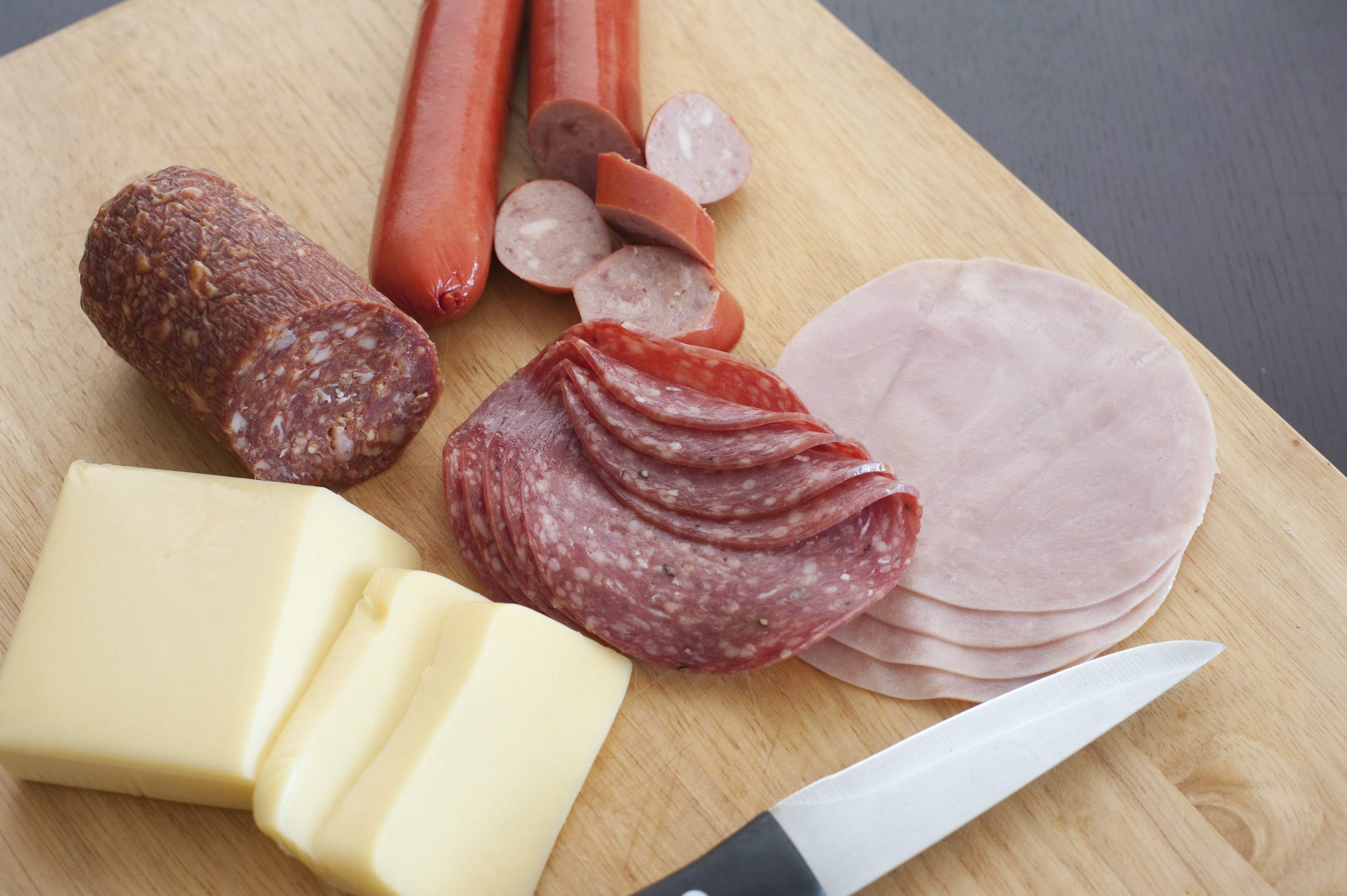 German breakfast with sliced spicy salami, ham, sausages and portions of cheese being prepared on a wooden chopping board with a knife
