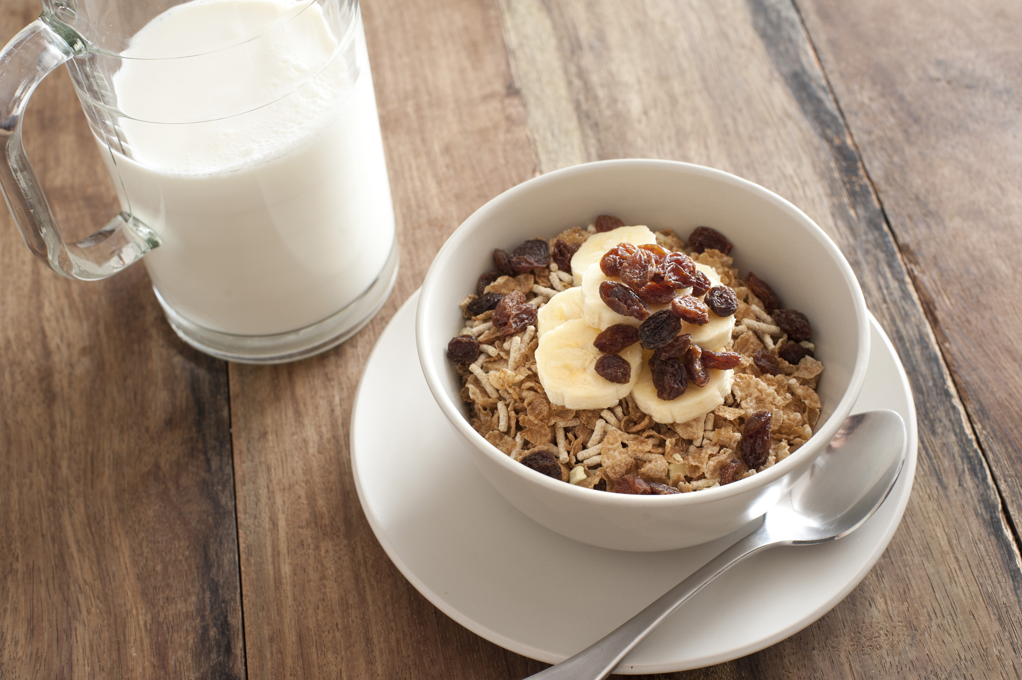 Healthy muesli topped with fresh sliced bananas and raisins served with milk for a tasty energising breakfast