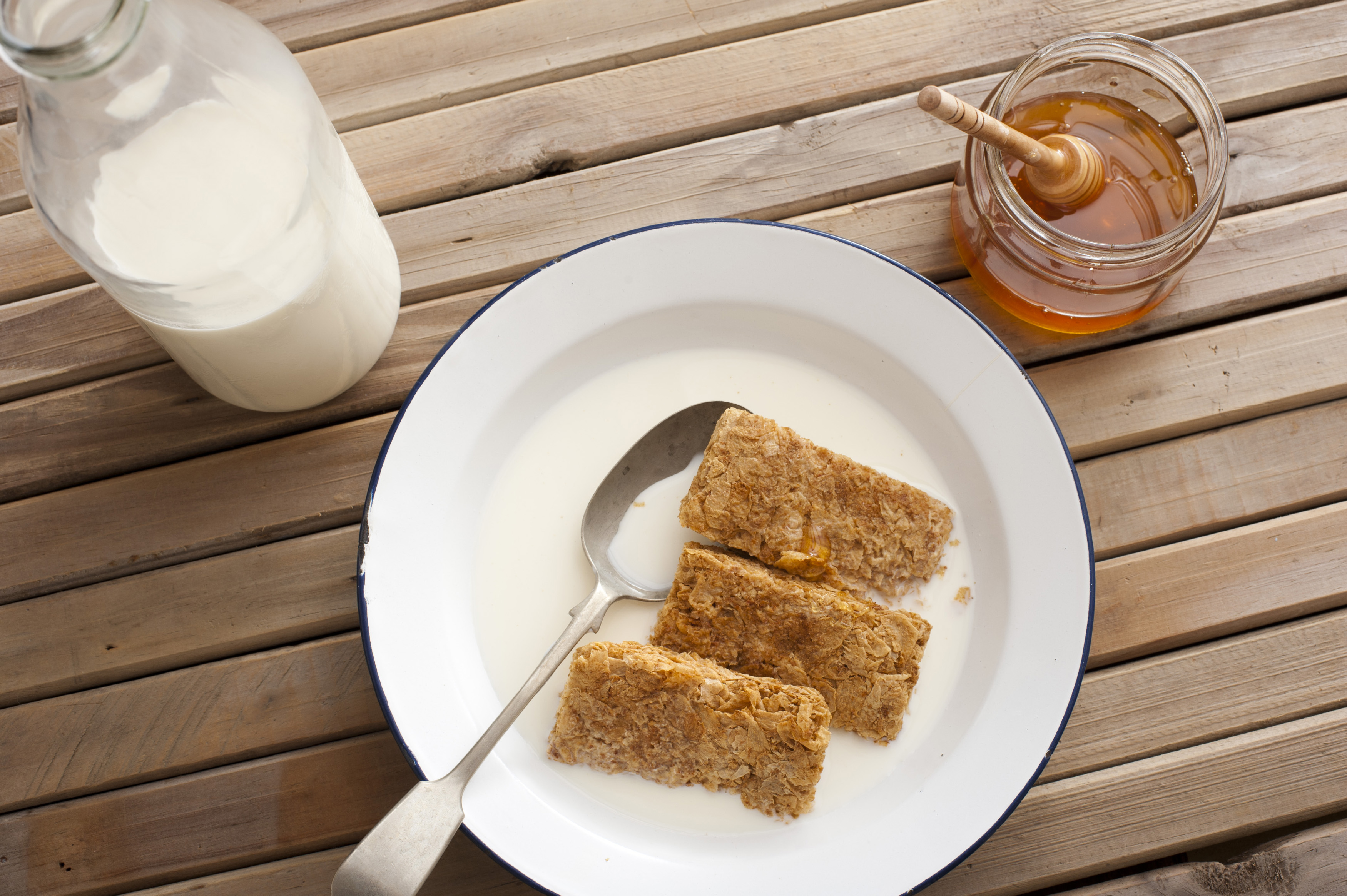 First person top down perspective view on whole wheat breakfast cereal bars in round bowl with honey and bottle of milk over table