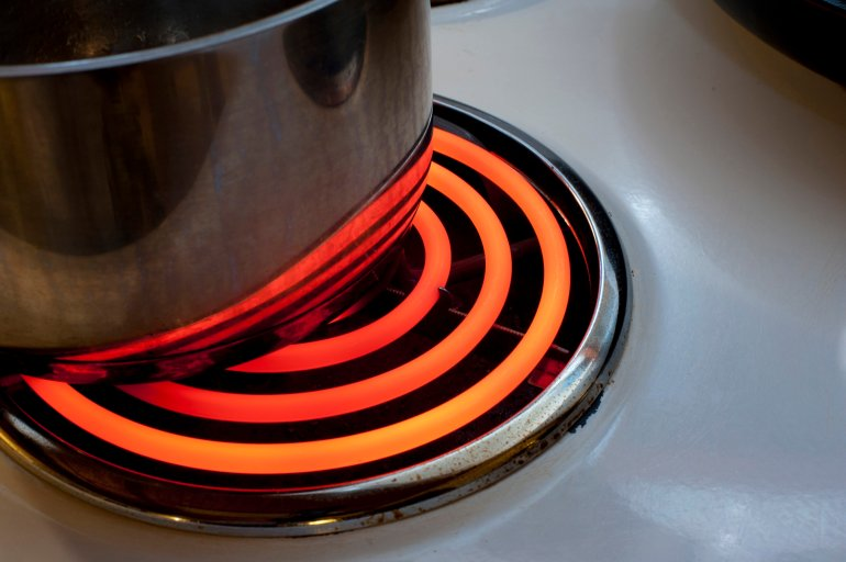 Cooking On The Red Hot Spiral Hotplate Of An Electric Stove With A Metal Pot Or