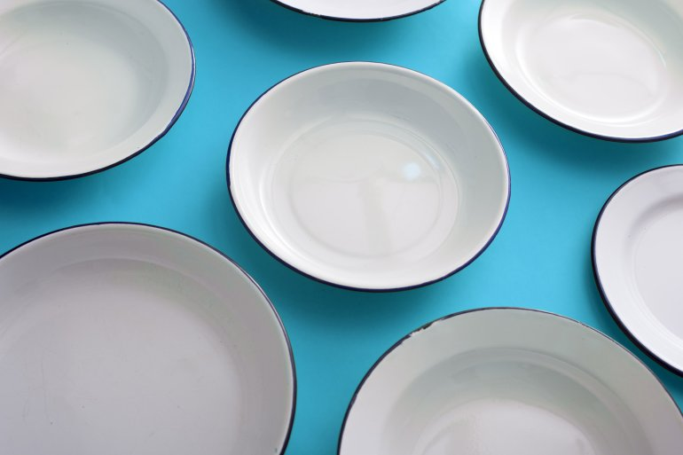 Set Of Tered Empty Clean White Enamel Metal Dinner Plates On A Blue Background In